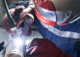 A welder wears a face-shield, protecting them from the bright light of the weld pool.