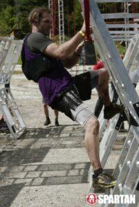man climbing white scaffolding for a spartan race