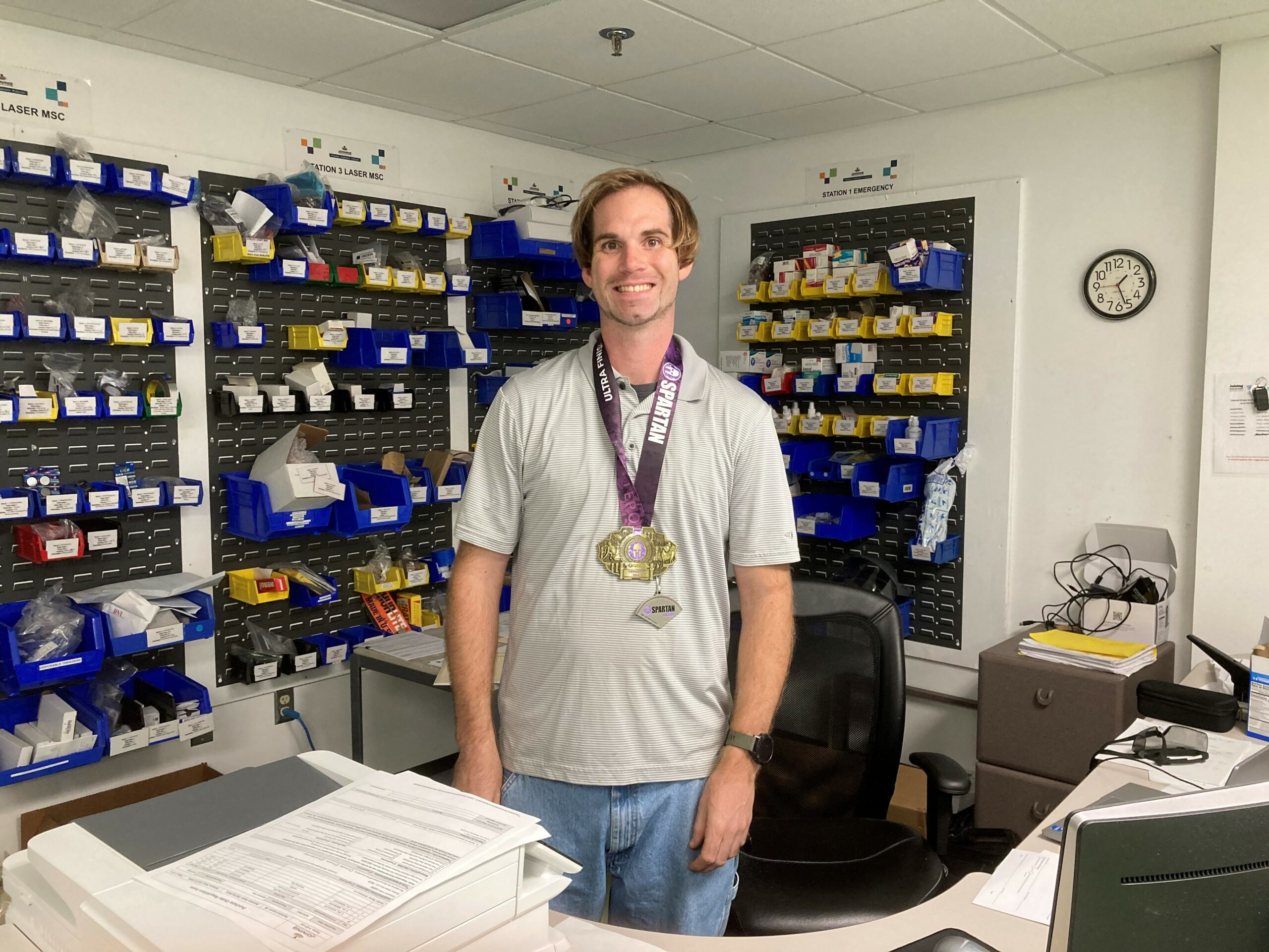 male employee poses with race medal