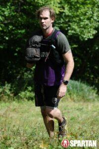 man moves through field with sandbag over shoulder