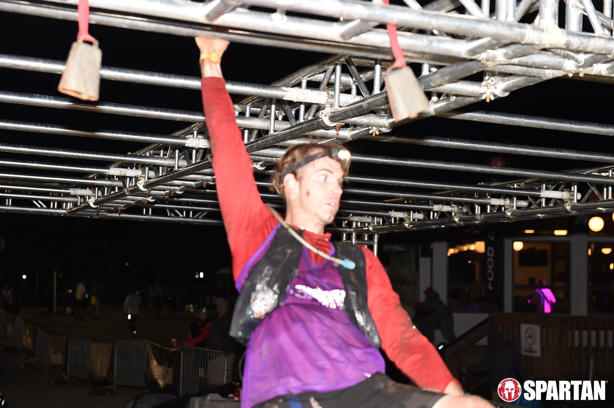 man with headlamp swings on monkey bars